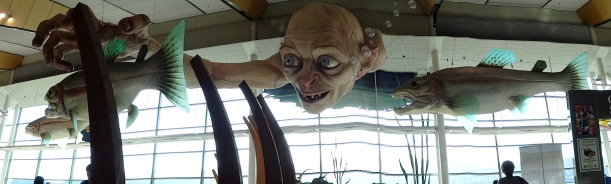 Gollum dunks his head underwater to catch a fish - where is the 'real'. Installation by Weta at Wellington Airport. Photo by Rui Martins